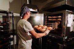 Knappe bakker in het eenvormige hoogtepunt van het holdingsdienblad van vers gebakken brood bij de productie stock foto