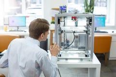 Knappe beambte die 3D printer bekijken Stock Fotografie