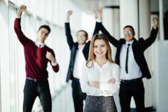 Knappe bedrijfs womanin voorzijde van zijn teamlid die hun voltooiing in bureau vieren royalty-vrije stock afbeelding