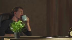 Knappe bedrijfsmens die bij notitieboekje op het moderne kantoor werken die coffe drinken Een succesvolle jonge ondernemer is stock video