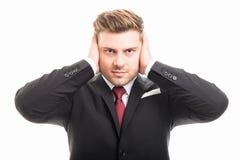 Knappe bedrijfsmens die oren zoals doof gebaar behandelen stock foto's