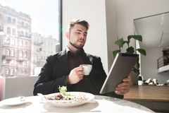 Knappe bedrijfsmens gebruikend een tablet en drinkend koffie bij een koffie stock fotografie