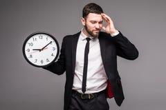 Knappe bedrijfsmens met in hand klok, droevige beasy met tijd, Royalty-vrije Stock Foto