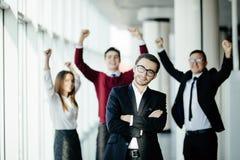 Knappe bedrijfsmens voor zijn teamlid die hun voltooiing in bureau vieren stock foto