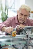 Knappe bejaarde het aanpassen extruder van 3D printer stock fotografie