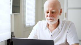 Knappe bejaarde hogere mens die aan laptop computer thuis werken Het verre freelance werk aangaande pensionering stock video