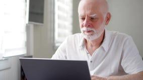 Knappe bejaarde hogere mens die aan laptop computer thuis werken Het verre freelance werk aangaande pensionering stock footage