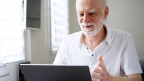 Knappe bejaarde hogere mens die aan laptop computer thuis werken Ontvangen goed opgewekt en gelukkig nieuws stock video