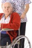 Knappe bejaarde in rolstoel met verpleegster Royalty-vrije Stock Afbeeldingen