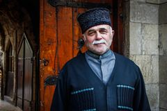 Knappe bejaardeglimlachen in nationaal Azeri kostuum, hoed en grijze snor stock fotografie