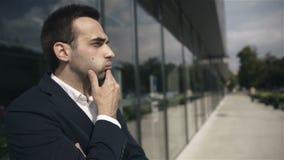Knappe betrokken zakenman die op iemand in openlucht het bureaugebouw wachten