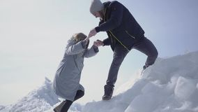 Knappe blonde gebaarde man die hand geven aan aantrekkelijke jonge vrouw die haar helpen om op het ijsblok te beklimmen Een paar stock footage