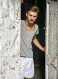 Knappe blonde jonge mens die oude deur openen Stock Foto's