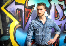 Knappe blonde jonge mens tegen kleurrijke graffitimuur Royalty-vrije Stock Foto's