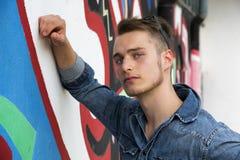 Knappe blonde jonge mens tegen kleurrijke graffitimuur Stock Afbeeldingen