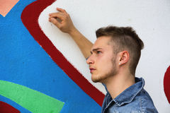 Knappe blonde jonge mens tegen kleurrijke graffitimuur Stock Foto