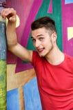 Knappe blonde jonge mens tegen kleurrijke graffitimuur Royalty-vrije Stock Afbeelding