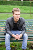 Knappe blonde jonge mensenzitting op parkbank Royalty-vrije Stock Foto's