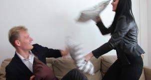 Knappe blonde man en aardige vrouw die hoofdkussenoorlog in bank hebben - vrouwenwinsten stock footage