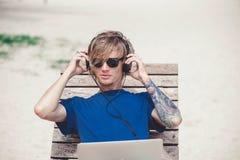 Knappe blondemens zonnebril dragen en een hoed die met laptop bij het strand werken royalty-vrije stock fotografie