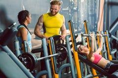 Knappe bodybuilder die met een mooie geschikte vrouw bij de geschiktheidsclub spreken stock foto's