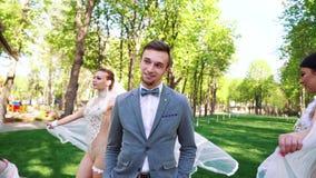 Knappe bruidegom die mooie bruiden bekijken die rond hem in zonnig park lopen stock footage