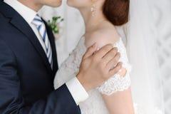 Knappe bruidegom die zacht mooie bruid houden door de schouder stock foto