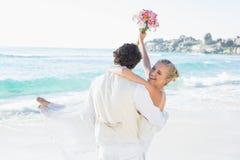 Knappe bruidegom die zijn mooie lachende vrouw vervoeren royalty-vrije stock afbeeldingen