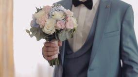 Knappe bruidegom met mooi huwelijksboeket Lichte achtergrond Langzame Motie stock video