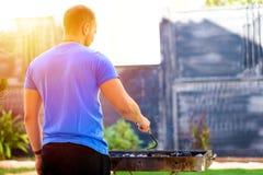 Knappe brutale gebaarde mensen kokende barbecue in openlucht stock afbeelding