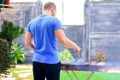 Knappe brutale gebaarde mensen kokende barbecue in openlucht royalty-vrije stock foto's