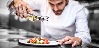 Knappe chef-kok gietende olijfolie op maaltijd stock foto