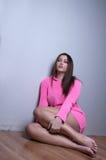 Knappe dame die breiende roze blouse dragen tegen huismuur Royalty-vrije Stock Foto's