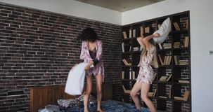 Knappe dames die over bed springen en met hoofdkussens in de ochtend vechten terwijl het dragen van pyjama's zijn zij zeer gelukk stock footage