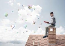 Knappe de lezingsboek en aerostaten die van de studentenkerel in lucht vliegen Stock Foto's