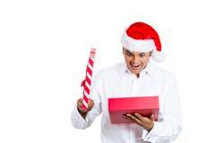 Knappe die mens over zijn aanwezige Kerstmis wordt opgewekt Stock Afbeelding