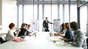 Knappe directeur die op flipchart tijdens een vergadering richten stock videobeelden