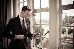 Knappe directeur die zich naast hotelvenster bevinden die zijn mobiel cellphoneapparaat met behulp van stock fotografie