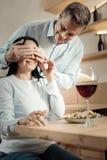 Knappe echtgenoot die tot verrassing maken aan vrouw stock afbeeldingen