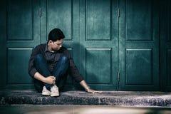 knappe eenzame mens in gefrustreerde depressiezitting alleen op Th Stock Foto