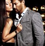 Knappe elegante man in kostuum met het mooie sexy vrouw stellen op de zwarte achtergrond van studiolichten stock afbeelding