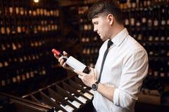 Knappe elegante mens die klanten helpen om wijn te kiezen stock foto's