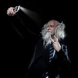 Knappe elegante oldman makend een selfie in studio Royalty-vrije Stock Afbeeldingen