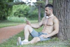 Knappe en aantrekkelijke spier jonge mens die in een park rusten en royalty-vrije stock foto's