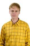 Knappe ernstige jonge mens in geel Stock Foto's