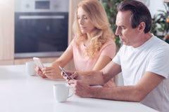 Knappe ernstige mens die op zijn telefoon worden geconcentreerd royalty-vrije stock afbeelding