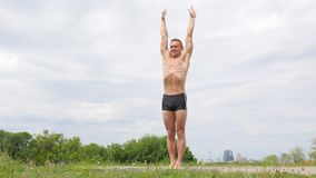 Knappe flexibele Atletische mens die yogaasanas in het park doen stock footage