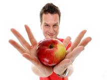 Knappe geïsoleerde mens in rood overhemd met appel Royalty-vrije Stock Foto's