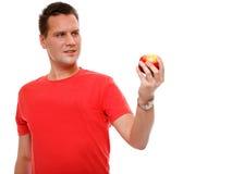 Knappe geïsoleerde mens in rood overhemd met appel Royalty-vrije Stock Foto