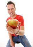 Knappe geïsoleerde mens in rood overhemd met appel Stock Foto